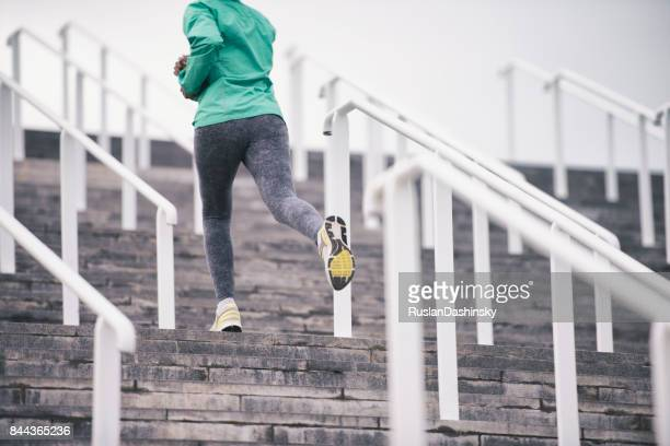 active female on the move upstairs. - buttock stock pictures, royalty-free photos & images