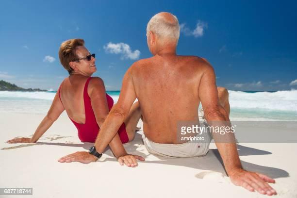 active fir senior couple relaxing on sunny sand beach