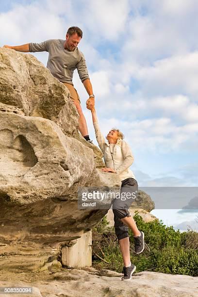 Activa en forma pareja madura ayudar a otros paseos de excursionismo