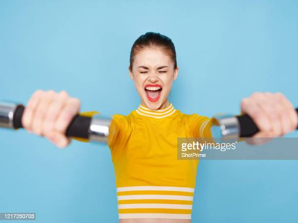 active girl in a tracksuit struggles doing exercises with dumbbells. - hands in her pants fotografías e imágenes de stock