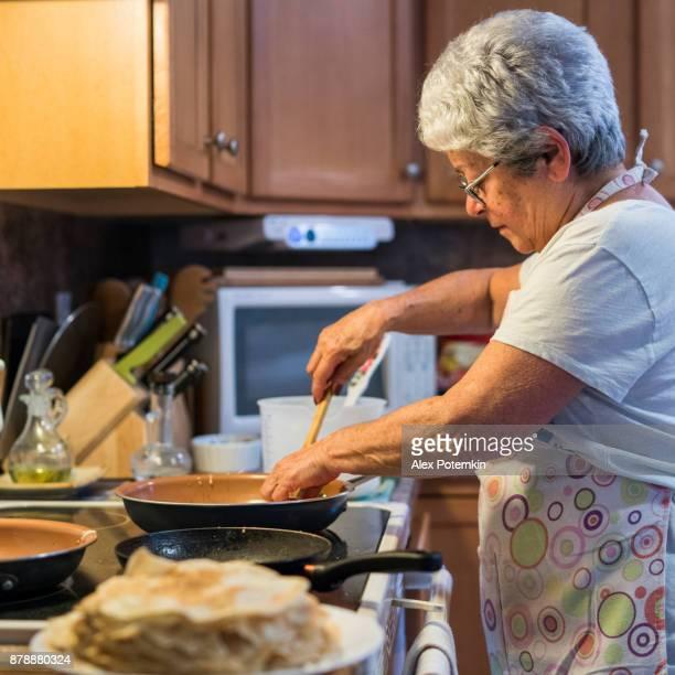 Actieve grootmoeder, zilveren haired 70-jaar-oud senior vrouw, pannenkoeken in de binnenlandse keuken koken voor ontbijt.