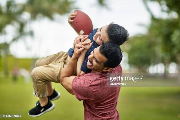 actieve spaanse familie die voetbal speelt bij het openbare park van miami - football player stockfoto's en -beelden