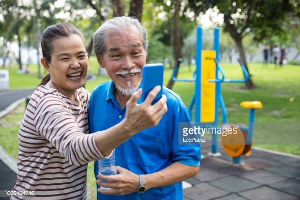 Active lifestyle, seniors taking a selfie after workout at the park