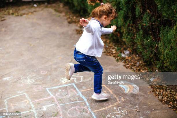 active little girl enjoying playing hopscotch - hopscotch stock pictures, royalty-free photos & images