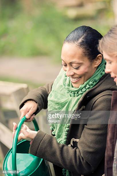 Active London Woman Waters Plants in Garden with Friend