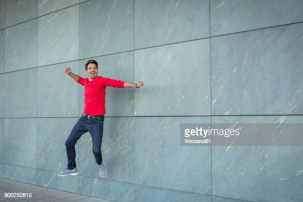 Active man jumping for joy, cheering