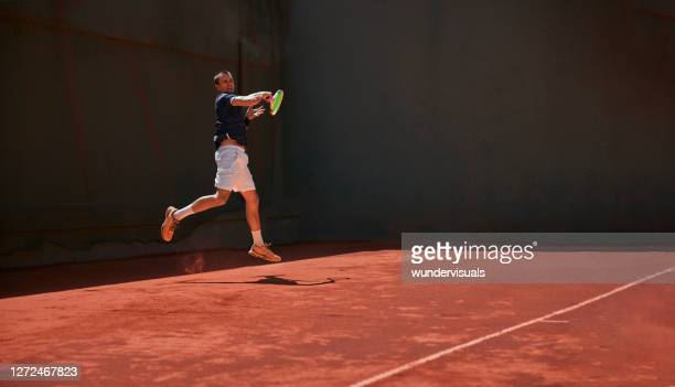 active man playing tennis match on clay court - tennis tournament stock pictures, royalty-free photos & images