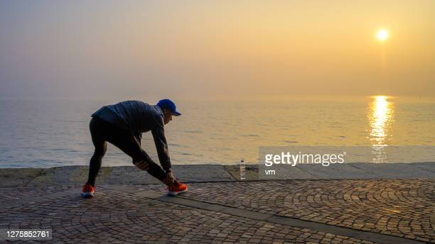 active man stretching his legs on a footpath next to the sea - warming up stock pictures, royalty-free photos & images