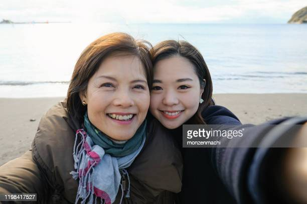 active mature woman and her daughter taking selfie on beach - self portrait photography stock pictures, royalty-free photos & images