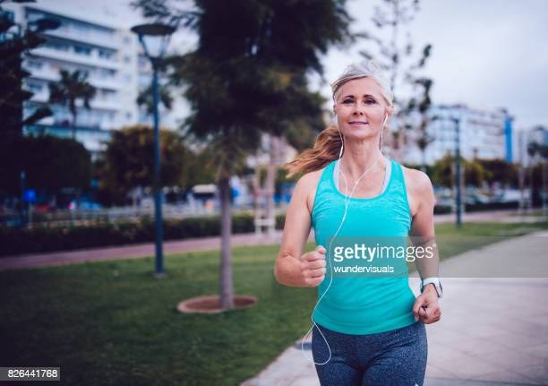 Active mature woman running with headphones and smartwatch in park