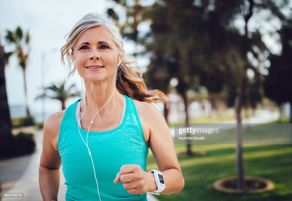 Active mature woman with headphones and smartwatch running in park : Stock Photo