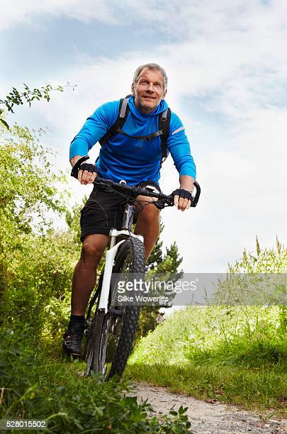 active middle-aged man cycling outdoors on a mountain bike - 50 54 jahre stock-fotos und bilder