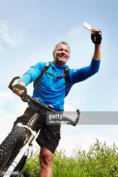 active middle-aged man cycling outdoors on a mountain bike