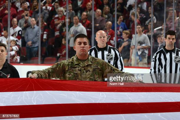 Active military personnel and veterans hold a large american flag over the ice before the start of a game between the Arizona Coyotes and Winnipeg...