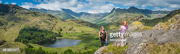 Active mother and daughter hiking in idyllic mountain scenery panorama