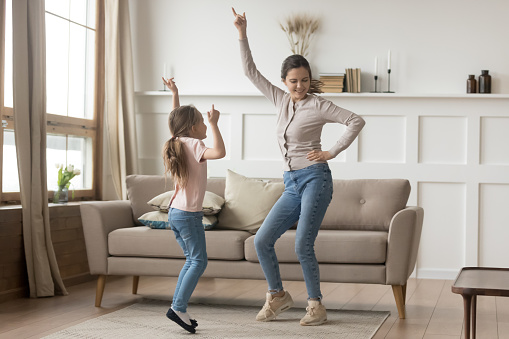 Active mother dancing at home with little daughter 1157439220