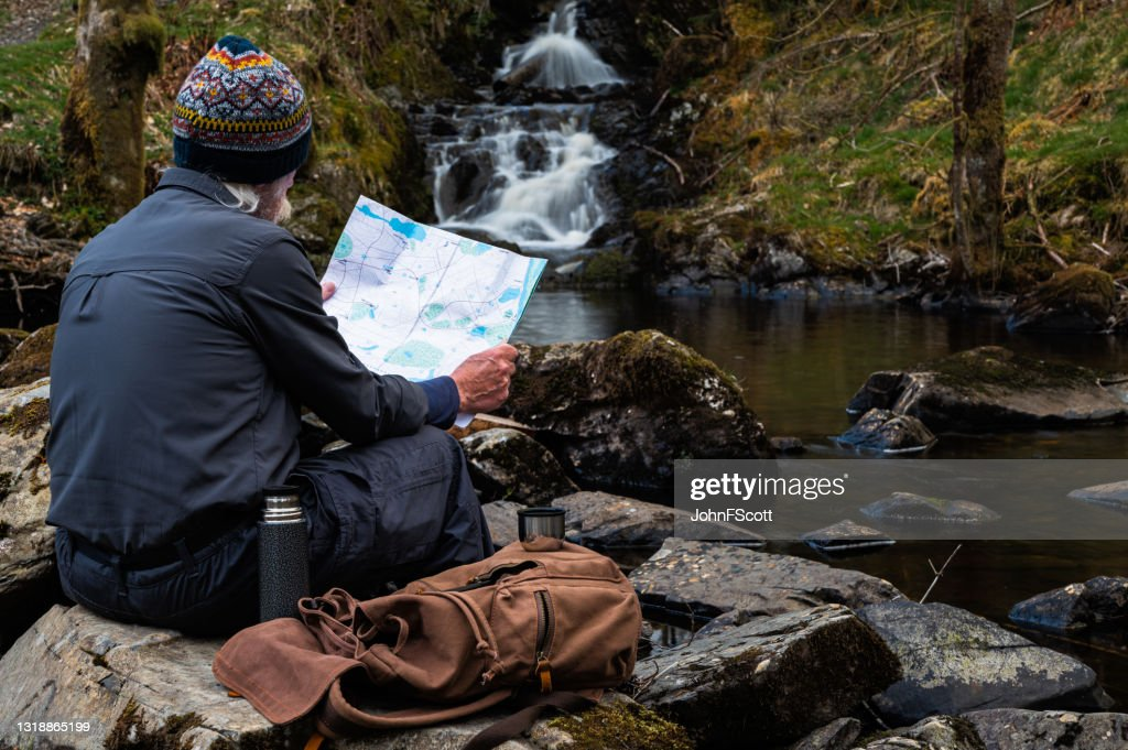 Active retired man checking his map : Stock Photo