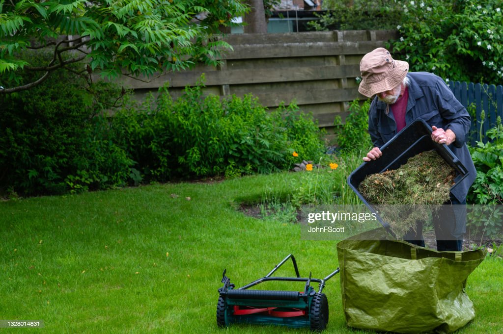 Active retired man emptying a grass box : Stock Photo