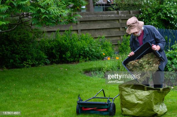 active retired man emptying a grass box - johnfscott stock pictures, royalty-free photos & images