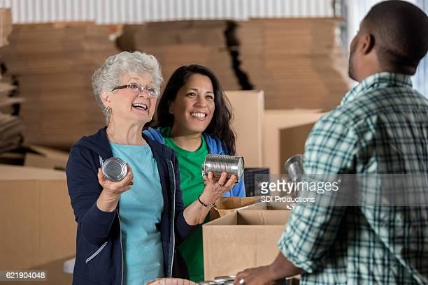 Active retired senior woman volunteers in food bank