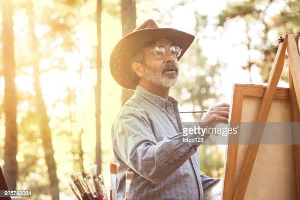 Active senior adult man enjoys art hobby outdoors.