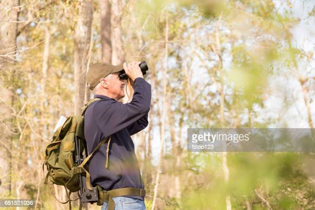 Active senior adult man hiking in woods, bird watching.