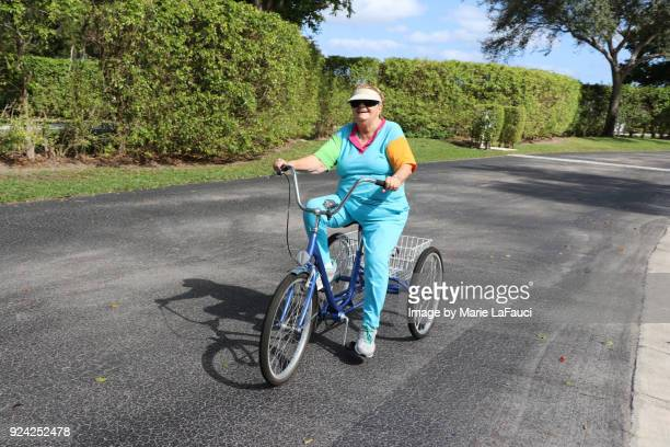 Active senior adult riding a three-wheeled bike