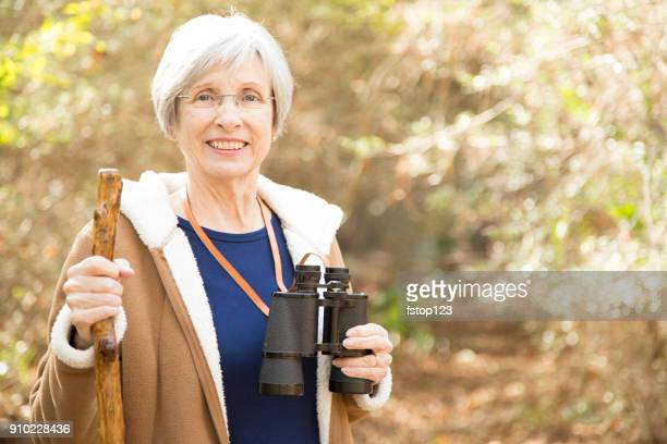 Active senior adult woman hiking in wooded area.