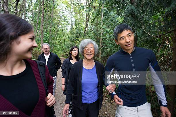 Active Senior Asian Woman Walking in Wooded Trail with Family