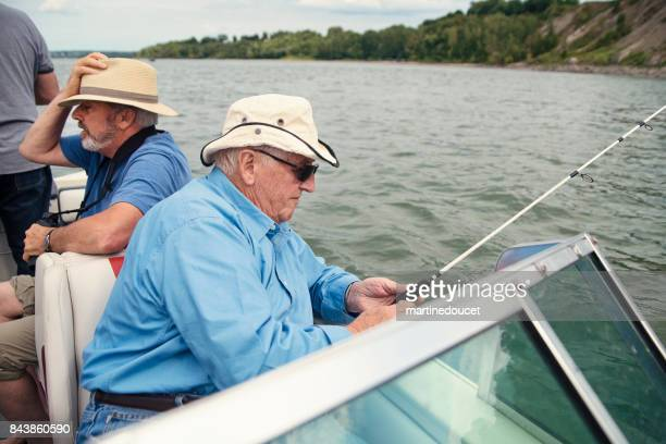 Active senior brothers with hat on a fishing boat.