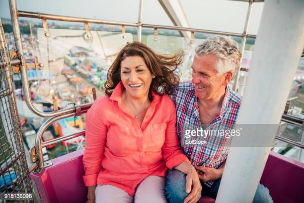 active senior couple at the fairground - ferris wheel stock pictures, royalty-free photos & images