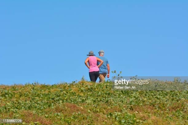 active senior couple hiking outdoors - rafael ben ari stock-fotos und bilder