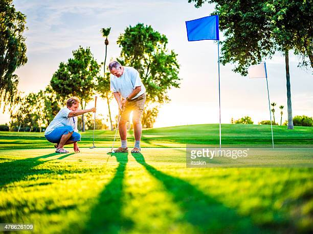 active senior couple playing golf - putting green stock pictures, royalty-free photos & images