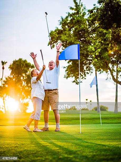 Active senior couple playing golf