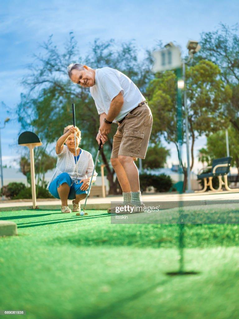 Active senior couple playing golf : Stock Photo