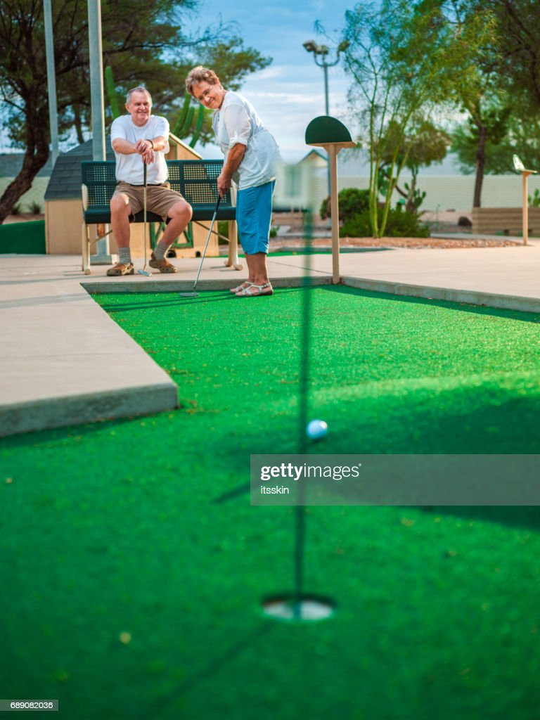 Active senior couple playing golf : Stock Photo