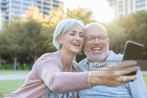 aktive senioren paar nehmen selfie - fotohandy stock-fotos und bilder