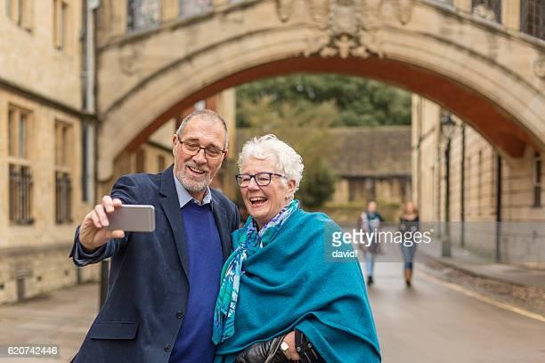 Active Senior Couple Taking Selfie at Bridge of Sighs