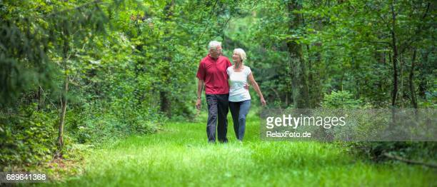 Active senior couple walking arm in arm through forest in summer