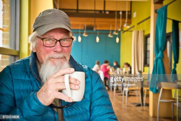 active senior enjoying coffee in cafe in montana - small town america stock pictures, royalty-free photos & images