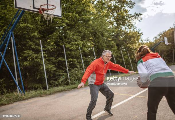 active senior father and daughter playing basketball - basketball hoop stock pictures, royalty-free photos & images