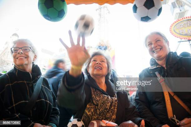 Active senior girlfriends at the fair in Amsterdam, throwing balls