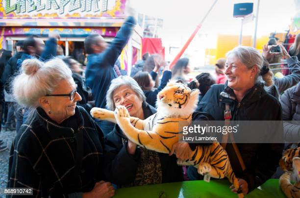 Active senior girlfriends at the fair in Amsterdam, winning a prize