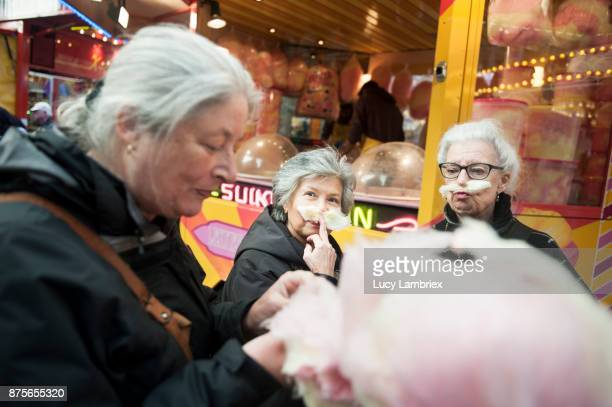 Active senior girlfriends enjoying cotton candy at the fair in Amsterdam