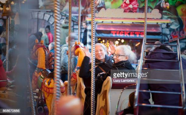 Active senior girlfriends in the merry-go-round at the fair in Amsterdam