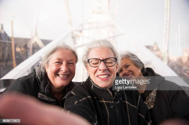 Active senior girlfriends taking a selfie at the fair in Amsterdam