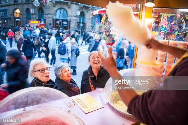 Active senior girlfriends waiting for their cotton candy at the fair in Amsterdam