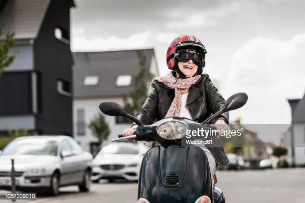 active senior lady riding motor scooter in the city - crash helmet stock pictures, royalty-free photos & images
