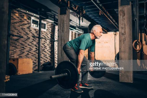 active senior male doing a deadlift exercise in a gym gym - weightlifting stock pictures, royalty-free photos & images