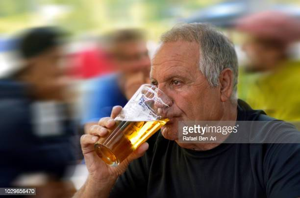 active senior male drinking beer - rafael ben ari stock pictures, royalty-free photos & images